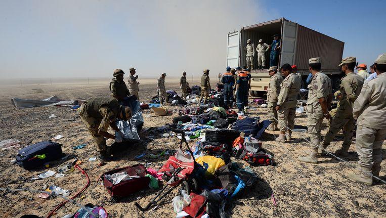 Russische reddingswerkers verzamelen samen met Egyptische soldaten persoonlijke bezittingen van passagiers van de gecrashte Airbus.