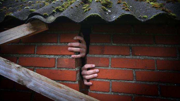 Handen zijn zichtbaar door een scheur in de muur van een woning in Bedum.