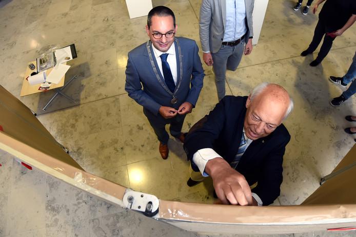 Samen met burgemeester Steven Adriaansen prikt Wim Adriaansen de eerste herinneringen aan de oorlog op de herinneringswand in het gemeentehuis van de gemeente Woensdrecht.