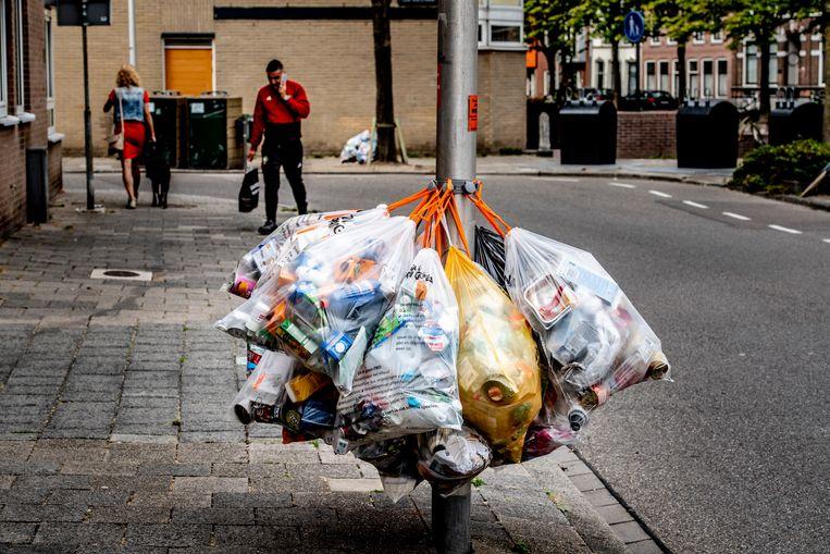 Vuilniszakken voor plastic afval aan een lantarenpaal in een woonwijk. Beeld null