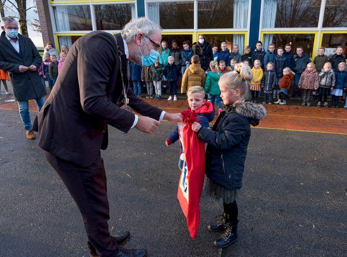 Isa en Jesse overhandigen burgemeester Victor Molkenboer een zak vol tekeningen voor Sinterklaas.