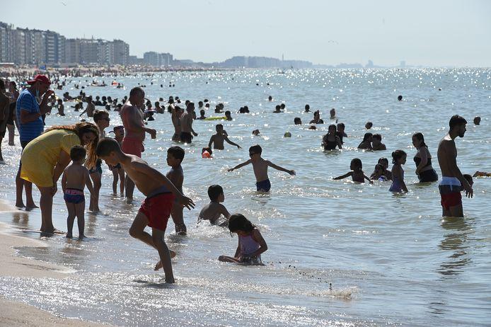 """Spelende kinderen wagen zich in zee in Oostende. """"Vermijd dit op piekmomenten"""", raadt Westtoer aan."""