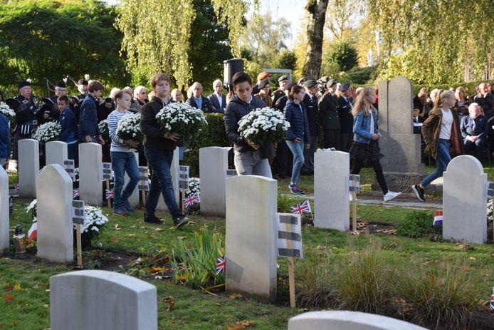 Kinderen van BS De Bron leggen bloemen bij de graven.  Een sfeervolle herdenking van oorlogsslachtoffers op het kerkhof in de Sint Janstraat in Goirle.
