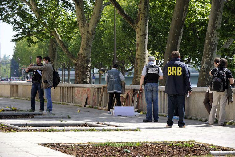 Politiemannen onderzoeken de omgeving van het museum. (AFP) Beeld