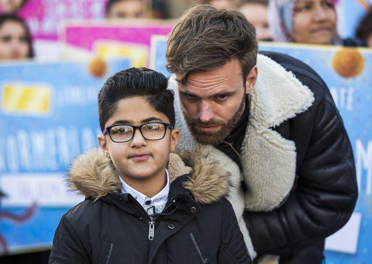 Programmamaker Tim Hofman en het Irakese jongetje Nemr tijdens de aanbieding van een petitie voor een kinderpardon, afgelopen november. Het pardon kwam er begin dit jaar. Beeld ANP