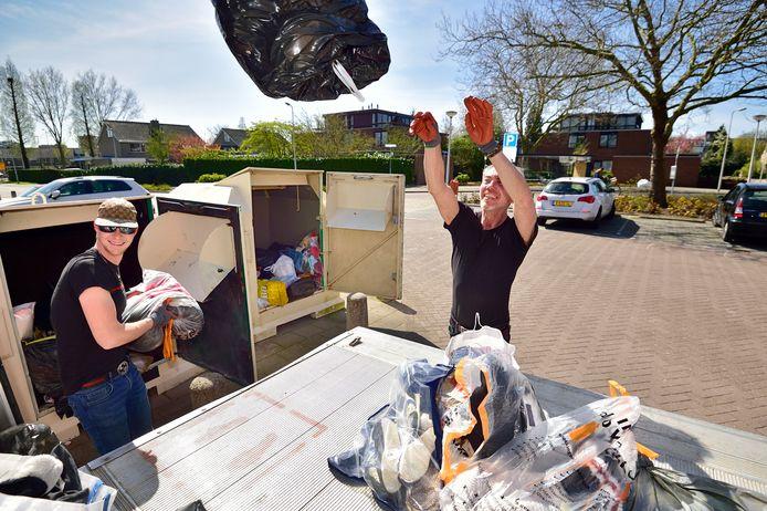 Medewerkers van Noppes Frenk en Kevin ( links ) maken kledingcontainer leeg in Gouda.
