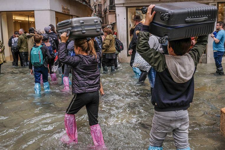 Koffers moeten noodgedwongen boven het hoofd worden gedragen.  Beeld Getty Images