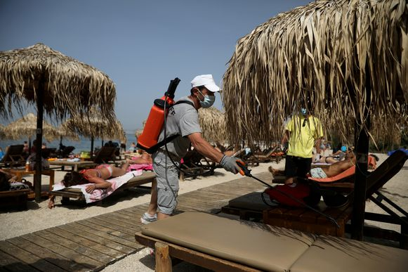 Tussen de zonnekloppers ontsmet een man ligstoelen op een strand in Athene.