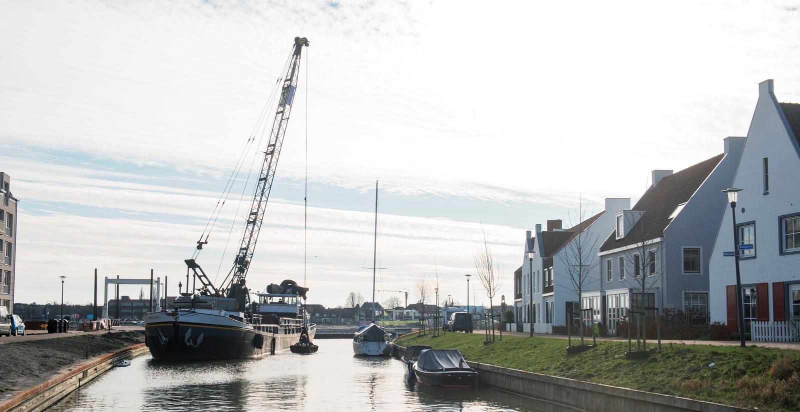 Vanaf het schip Poolster wordt de nieuwe gracht tussen de straten Robbenzand (rechts) en Waterstad Boulevard (links) in het Waterfront hier en daar verder op diepte gebracht. Op de achtergrond is de bebouwing zichtbaar op de hoek van de Strandboulevard en de Havendam.