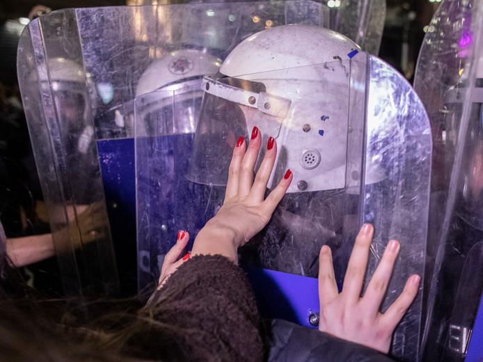 Duizenden vrouwen roepen leuzen tegen agenten die hen de weg versperren.