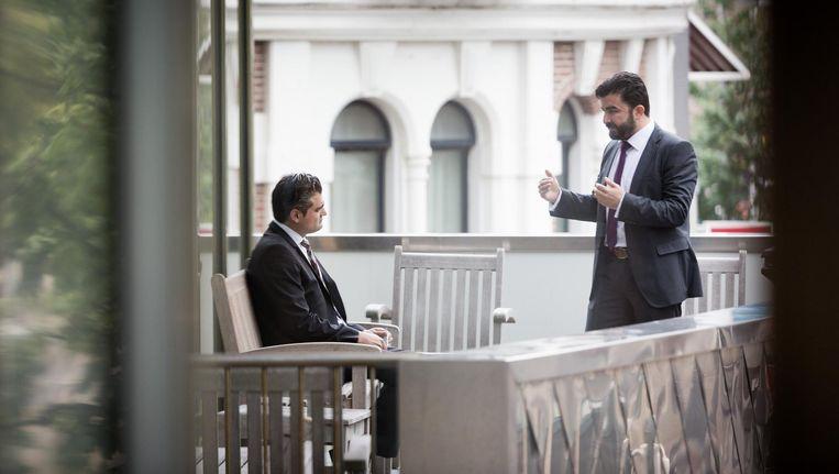 Tunahan Kuzu en Sulçuk Öztürk van Denk overleggen op het balkon van het ledenrestaurant van de Tweede Kamer. Beeld Freek van den Bergh / de Volkskant