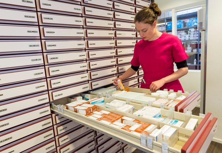 Een apothekersassistente zoekt medicijnen bij elkaar. Stijgende medicijnprijzen en nieuwe, vaak dure behandelingen voor ernstige ziekten veroorzaken volgend jaar een premiestijging van 30 euro. Beeld ANP