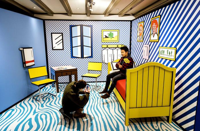 """Bezoekers van de tentoonstelling """"Rockstars of Art""""  in het MOCO Museum in Amsterdam maken een foto bij één van de werken van kunstenaar Roy Lichtenstein. Foto: koen van Weel"""