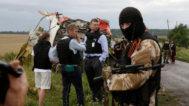 Een pro-Russische separatist staat bij een groepje OVSE-waarnemers. Beeld AP
