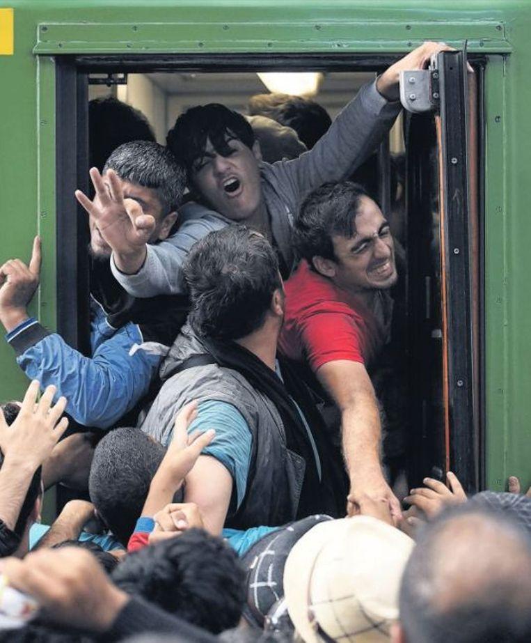 Migranten klimmen in een trein op het station van Boedapest. Beeld epa
