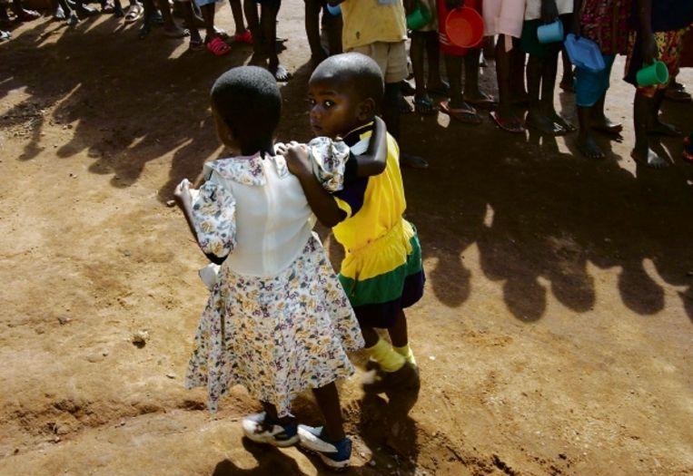 Twee aidswezen lopen naar de rij voor het eten bij hun weeshuis in Golomolo, Oeganda. (FOTO EPA) Beeld EPA