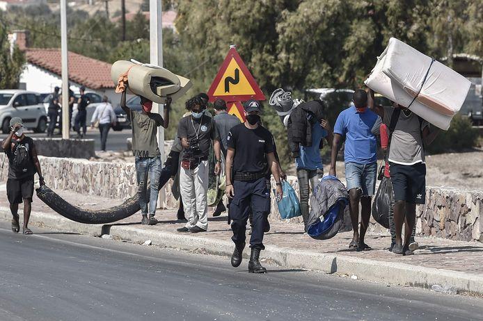Een politieman begeleidt migranten met hun spullen naar het nieuwe tijdelijke kamp dat wordt gebouwd op Lesbos, waar kamp Moria in de nacht van dinsdag op woensdag door brand is verwoest.