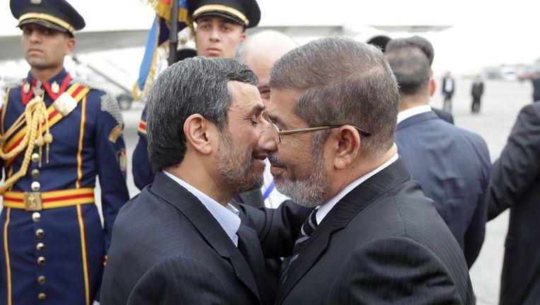 Morsi (rechts) ontving Ahmadinejad gisteren met rode loper en militaire erewacht. Beeld ANP