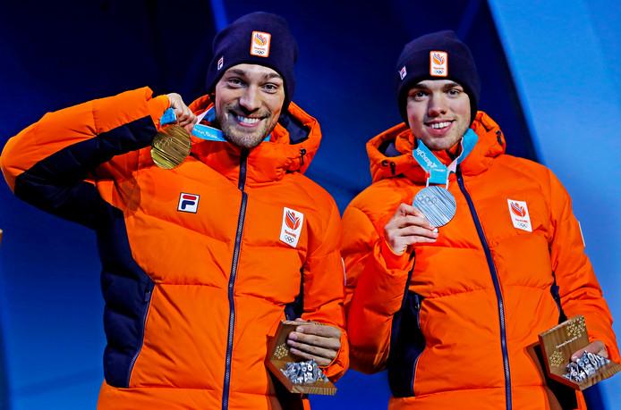 Kjeld Nuis bijt in de gouden medaille na zijn winst op de 1500 meter met naast zich zilveren medaille-winnaar Patrick Roest