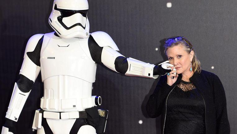 Carrie Fisher met een Stormtrooper bij de Europese première van Star Wars: The Force Awakens in 2015. Beeld epa