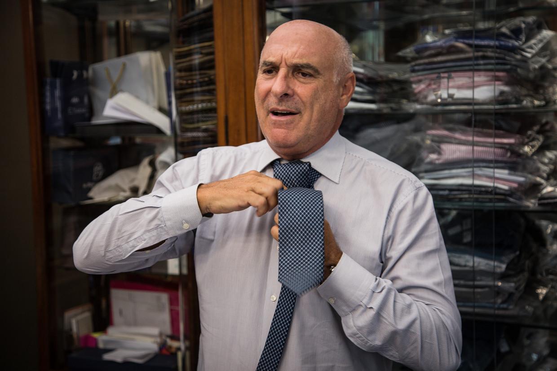 Maurizio Marinella strikt een van zijn zijden dassen om in zijn traditionele winkel in Napels.