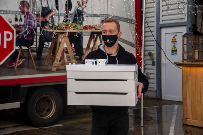 Matthias zet alle bestellingen in de koffer van de wagen in de drive-in.
