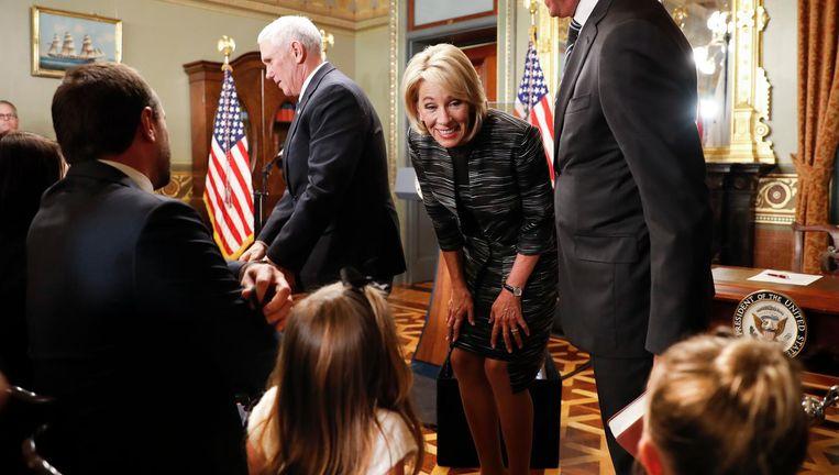 Betsy DeVos (midden) begroet kinderen en andere gasten na haar beëdiging door vicepresident Mike Pence (staand links). Beeld null
