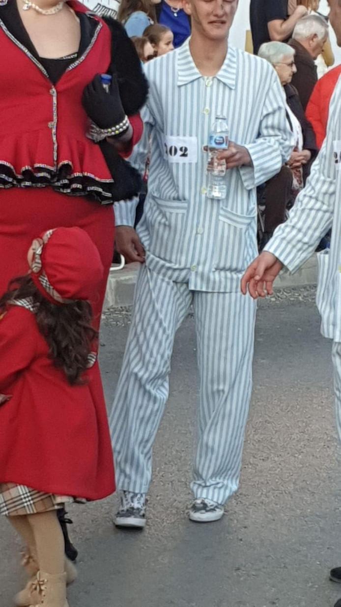 Een deelnemer aan de carnavalsoptocht is verkleed als concentratiekampgevange.