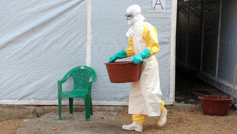 Een lid van Artsen zonder Grenzen werkt in beschermende kleding in een geïsoleerd gebied in Guinee, het eerste land waar de ebola-epidemie uitbrak. Beeld anp