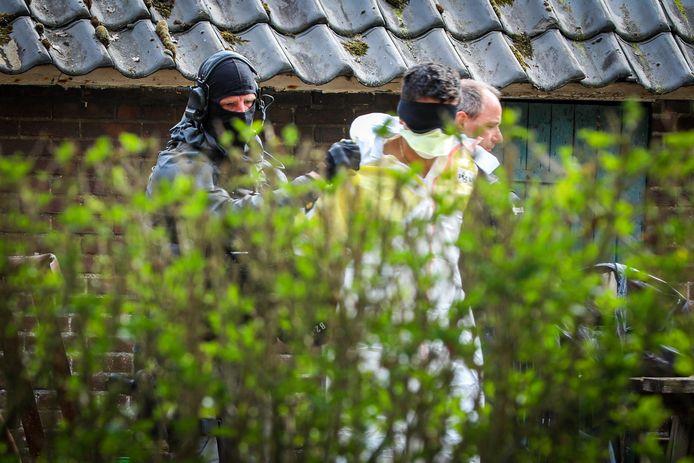 Zwaarbewapende agenten voeren een van de verdachten af bij de inval in het drugspand in Drempt.