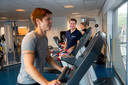 Fysiotherapeut Maarten Ruijs begeleidt mensen in de sportzaal waar ze werken aan hun revalidatie.
