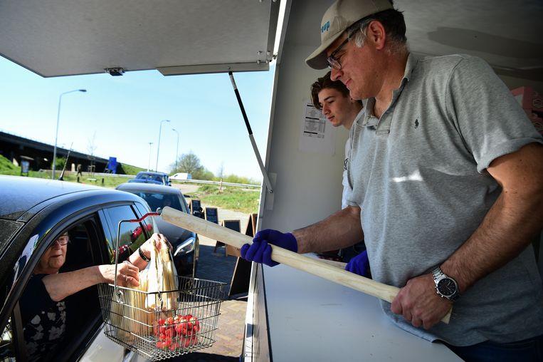 Corné Ooms, aspergeteler, reikt een van zijn klanten een bestelling aan, in zijn drive-thru in Hoogerheide. Naast asperges zijn ook aardbeien, beenham en eieren verkrijgbaar. Beeld Marcel van den Bergh / de Volkskrant