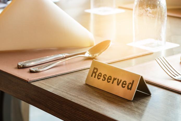 Een tafel waar het kaartje 'gereserveerd' op blijft staan kost een ondernemer omzet.