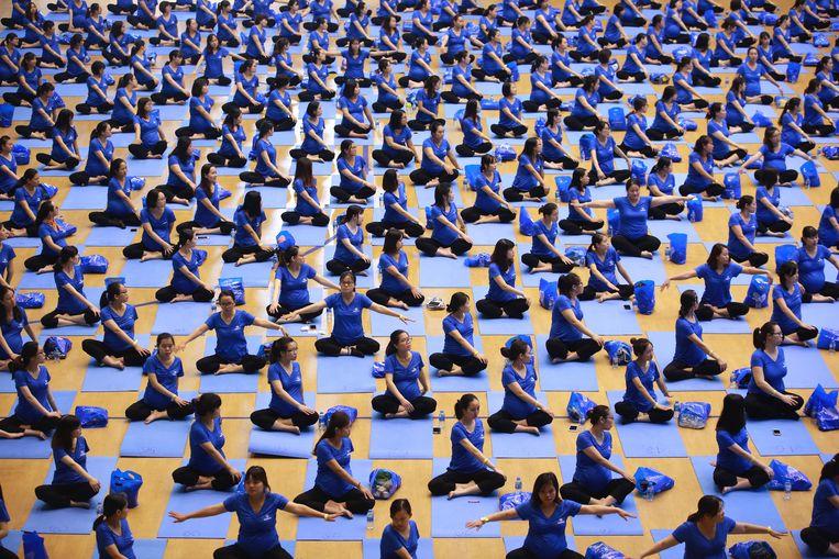 Meer dan vijfhonderd zwangere vrouwen tussen twintig en dertig jaar beoefenen yoga in het Quan Ngua stadion in Hanoi, Vietnam. Yoga wint aan populariteit onder Vietnamezen. Zij prijzen vooral de gunstige effecten voor  de fysieke en mentale gezondheid.  Beeld EPA
