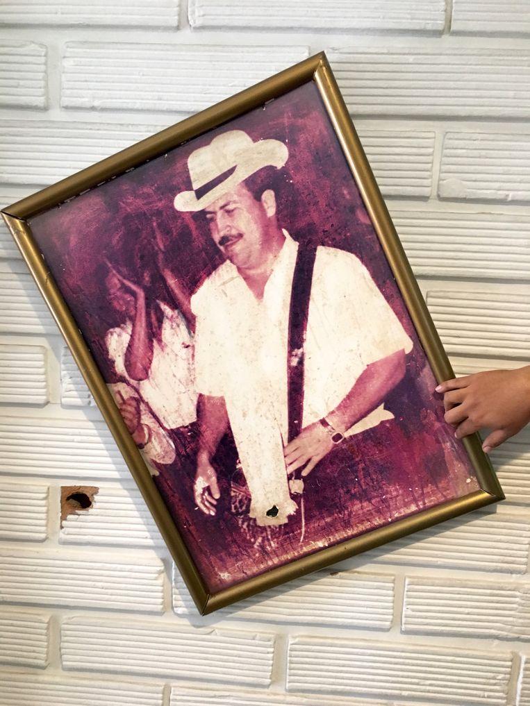 Een kogelgat in een van de huizen van de familie Escobar, achter een portret van Pablo Beeld Haroon Ali