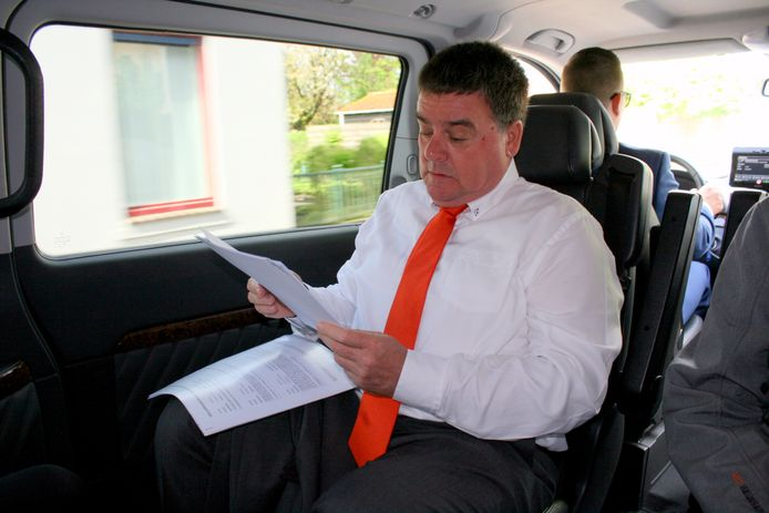Wethouder Jaap Kamp bereidt zich in de taxi voor op het laatste lintje dat hij mag opspelden.