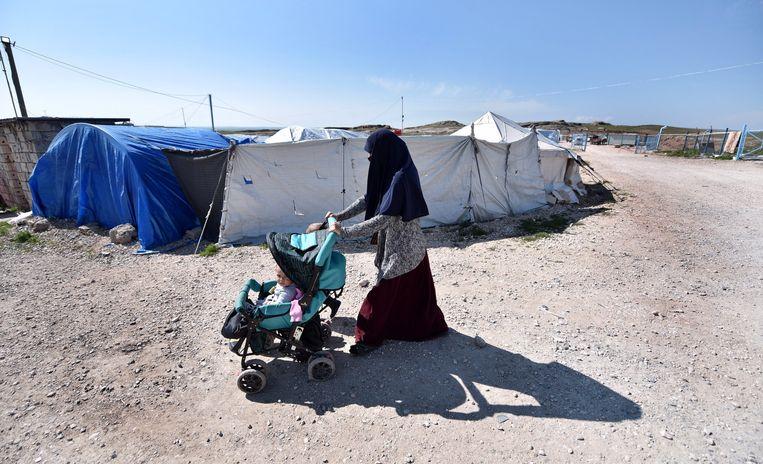 Een Nederlandse Syriëganger wandelt met haar twee kinderen door het vluchtelingenkamp Al Roj. Beeld EPA