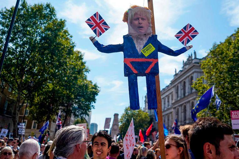 Demonstranten in Londen lopen met een bord met een foto van premier Boris Johnson. Beeld AFP