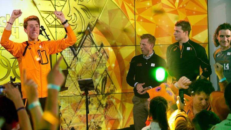Jorrit Bergsma (l) bouwt een feestje in het Holland House. Rechts Jochem Uitdehaage, Sven Kramer en Bob de Jong (vlnr.) Beeld anp