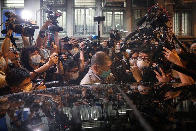 Jimmy Lai omringd de pers nadat hij is vrijgelaten door de politie.  Beeld EPA