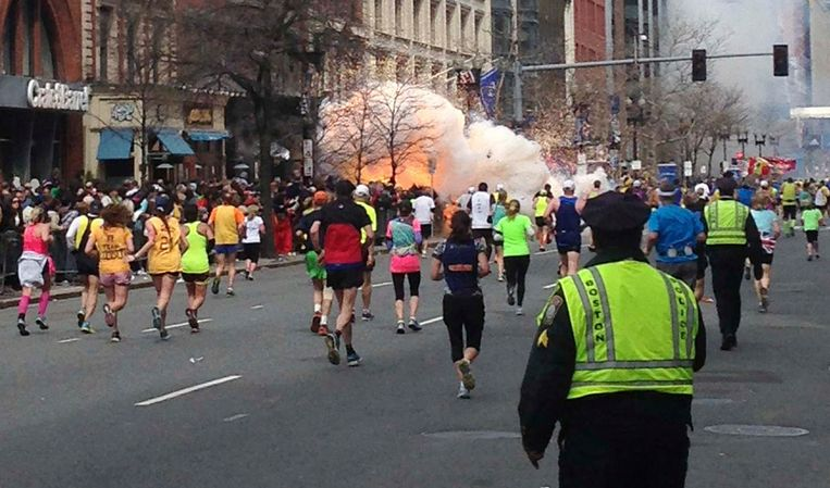 Runners continue to run towards the finish line of the Boston Marathon as an explosion erupts near the finish line of the race (2013). Beeld reuters