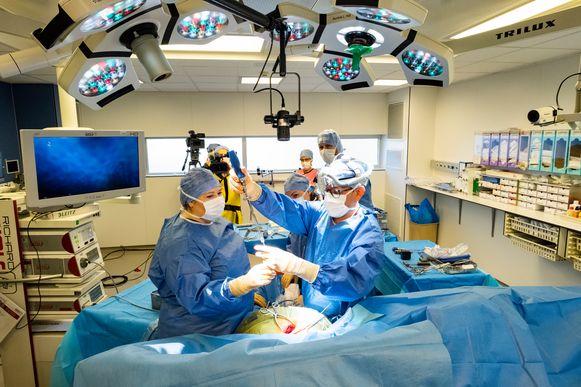 Dr. Mahieu voert een operatie uit. Dankzij de camera boven de operatietafel kunnen chirurgen de nieuwe techniek volgen.