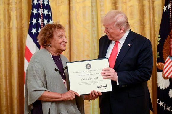 Donald Trump overhandigt een huldigingscertificaat aan Minnie Grant, moeder van de even aangehouden Christopher Grant.