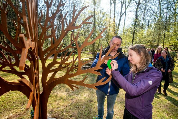 Carla en Alexander van Essen hangen het blaadje met daarop de naam van hun overleden dochter Linde in de gedenkboom.