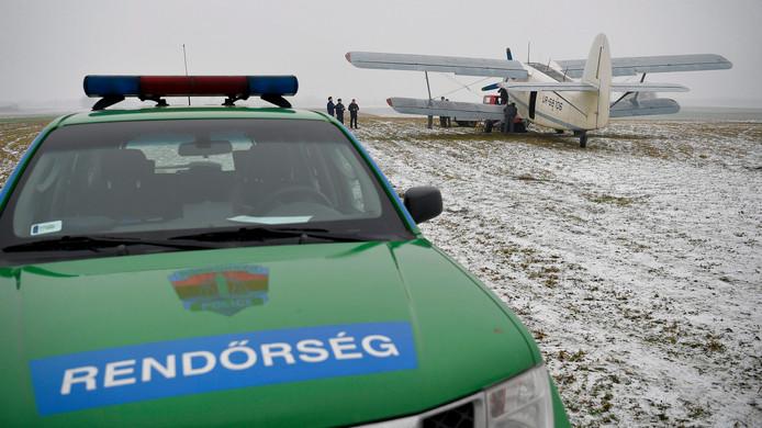 Hongaarse politieagenten onderzoeken een Oekraïens propellervliegtuigje dat in de buurt van Kallosemjen, 242 km ten oosten van Boedapest landde op een weiland. De 11 inzittenden, drie afghaanse en acht Vietnamese migranten werden na een zoektocht met honden en warmtecamera's in de buurt aangehouden. Foto Zsolt Czegledi