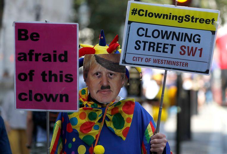 Een man protesteert als clown met een Boris Johnson masker op voor Downing Street 10.  Beeld AP