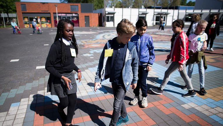 Leerlingen uit De Aker (in jeans) maken kennis met kinderen uit Holendrecht (in uniform). Beeld Rink Hof