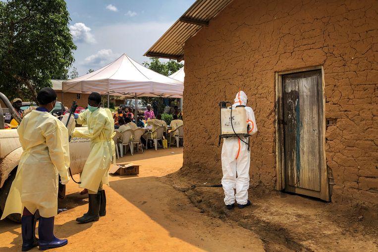 Een medewerker van de WHO ontsmet de deur van een huis in het dorp Mabalako in Congo waar twee gevallen van ebola zijn geconstateerd. Beeld AP