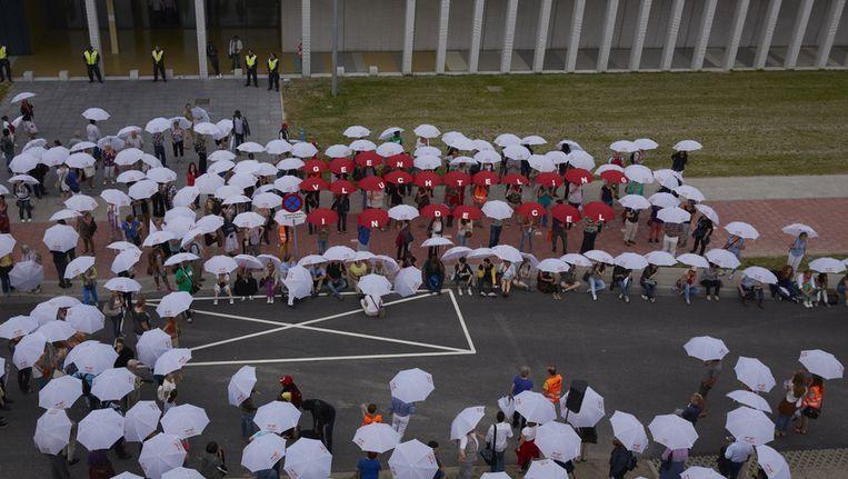 Zo'n driehonderd mensen demonstreren met witte paraplu's bij het Grensdetentiecentrum om aandacht te vragen voor vluchtelingen die na aankomst op Schiphol gelijk in detentie worden gezet. Beeld ANP
