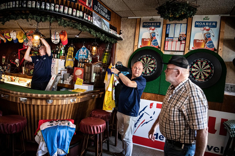 Henny Heutinck (achter de bar) en Henri Weikamp (midden) maken het café klaar voor de tour. Een deelnemer aan de Tour de Mariënvelde komt net binnen.